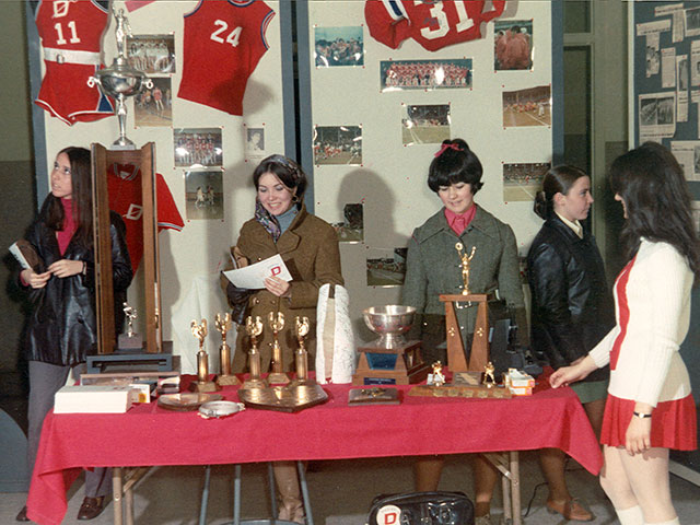 Five young girls admiring the trophies, photos and other items in the team colours at the Cégep de Trois-Rivière