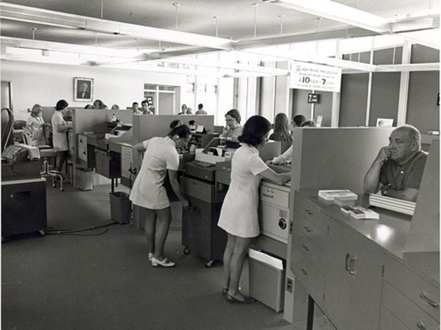 Women working at the counter of the Caisse populaire de Charlesbourg in the Québec region in the early 1970s