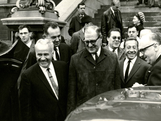 The photo features Gérard Filion in the company of Montréal Mayor Jean Drapeau and representatives of the French companies during a negotiation meeting